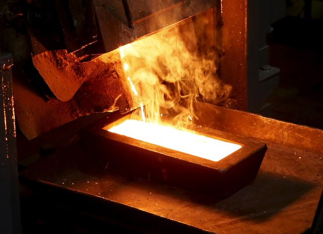 A melter casts an ingot of 92.96 percent pure gold at a procession plant of the Olimpiada gold operation, owned by Polyus Gold International company, in Krasnoyarsk region, Eastern Siberia, Russia, June 30, 2015. (Photo by Ilya Naymushin/Reuters)