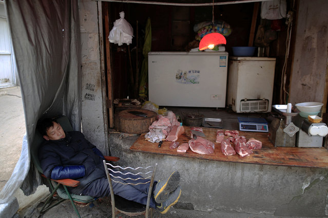A vendor selling pork takes a nap at a half-demolished house at Guangfuli neighbourhood in Shanghai, China, March 24, 2016. (Photo by Aly Song/Reuters)