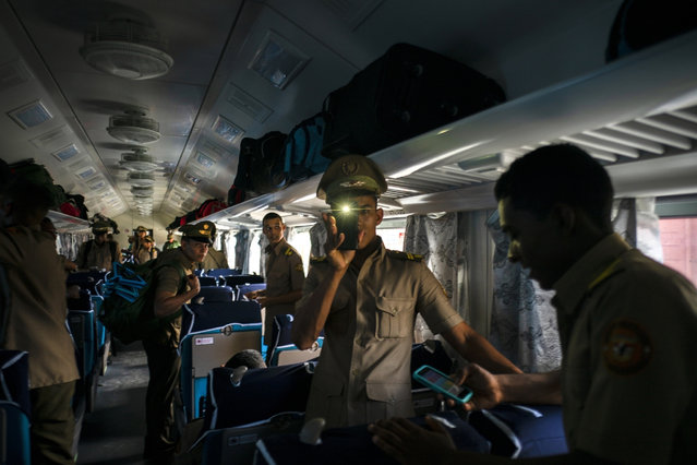 Cadets board the first train using new equipment from China, in Havana, Cuba, Saturday, July 13, 2019. The first train using new equipment from China pulled out of Havana Saturday, hauling passengers on the start of a 915-kilometer (516-mile) journey to the eastern end of the island as the government tries to overhaul the country's aging and decrepit rail system. (Photo by Ramon Espinosa/AP Photo)