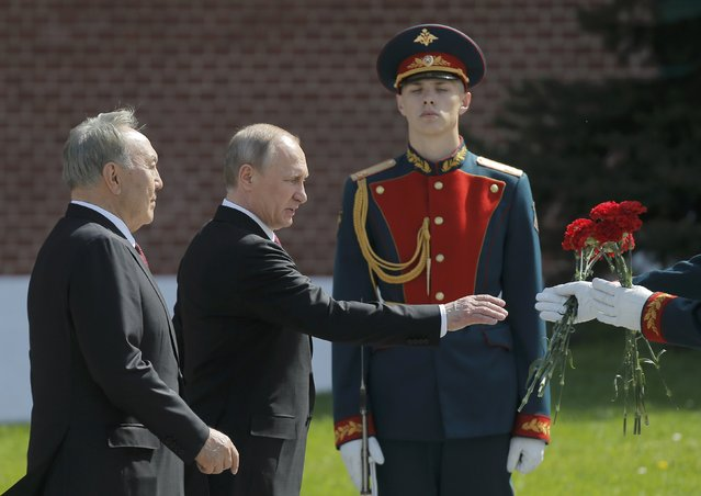 Russian President Vladimir Putin and Kazakh President Nursultan Nazarbayev attend a wreath-laying ceremony to mark the 71st anniversary of the victory over Nazi Germany in World War Two, at the Tomb of the Unknown Soldier by the Kremlin walls in Moscow, Russia, May 9, 2016. (Photo by Maxim Shemetov/Reuters)
