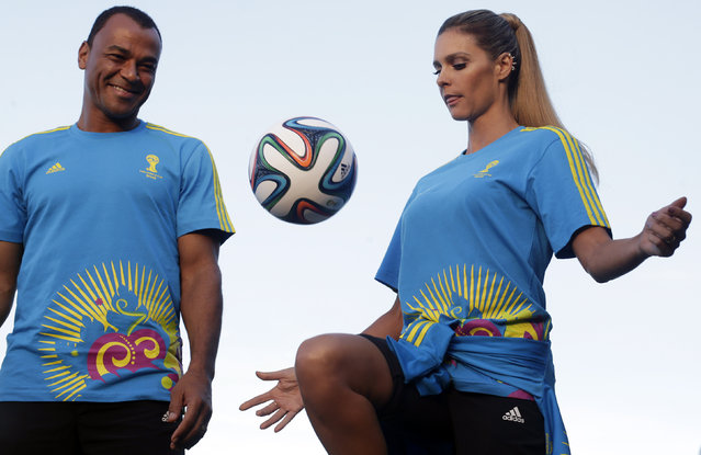 Former Brazilian soccer player Cafu (L) looks at Brazilian model Fernanda Lima as they present the uniforms for World Cup 2014 volunteers during Fashion Rio in Rio de Janeiro April 10, 2014. (Photo by Ricardo Moraes/Reuters)