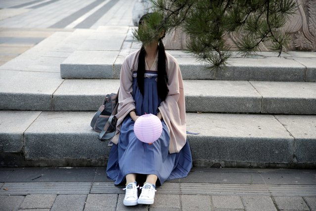 """A girl dressed in """"Hanfu"""" sits on a step as she waits to attend an event marking the traditional Qixi festival at a park in Beijing, China, August 7, 2019. Many Hanfu followers like the clothes for the fashion statement, but some, say its significance is greater. """"It's to propagate China's traditional culture"""", said another girl, who only gave her surname, Li. (Photo by Jason Lee/Reuters)"""