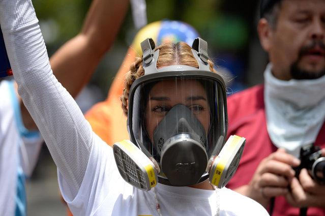 Lilian Tintori, wife of jailed Venezuelan opposition leader Leopoldo Lopez, gestures during a rally against Venezuelan President Nicolas Maduro in Caracas on April 19, 2017. Clashes broke out Wednesday at massive protests against Maduro, as riot police fired tear gas to push back stone- throwing demonstrators and a young protester was shot dead. Violence erupted when thousands of opposition protesters tried to march on central Caracas, a pro- government bastion where red- clad Maduro supporters were massing for a counter- demonstration. (Photo by Federico Parra/AFP Photo)
