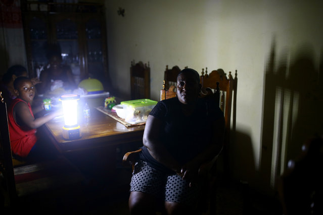 """In the April 17, 2019 photo, Jennifer Jean sits with her family in the living room of her home, lit only by camping lantern, in Port-au-Prince, Haiti. Since the blackouts started Jean's fledgeling catering business has cratered, making it impossible to do basic activities. Without refrigeration, she now has to buy ice on the street to keep her prepared food cool. """"Back in the day you were able to take your car out any time of night, 1 a.m. or 2 a.m."""", said Jean, who is thinking of migrating to the United States. """"Now all the streets are dark. You just don't know what you are going to run into"""". (Photo by Dieu Nalio Chery/AP Photo)"""