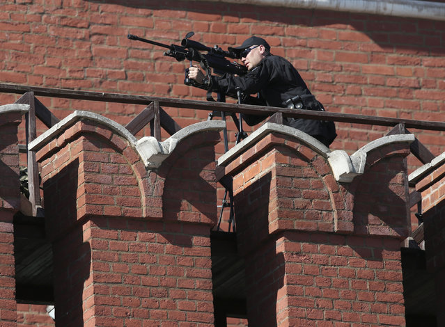 A sniper looks through his sight on the Kremlin wall during the Victory Day parade in Moscow's Red Square May 9, 2014. (Photo by Sergei Karpukhin/Reuters)