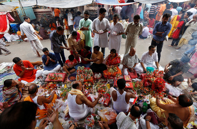 Hindu devotees worship idols of Hindu god Ganesh, the deity of prosperity, and goddess of wealth Laxmi, during a ritual on the first day of the Bengali New Year inside a temple in Kolkata, April 15, 2017. (Photo by Rupak De Chowdhuri/Reuters)