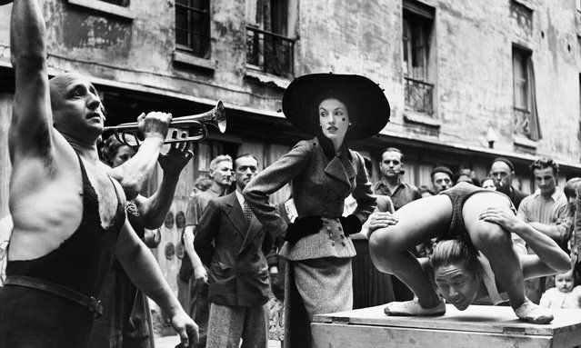 Model Elise Daniels dons a Balenciaga suit while surrounded by street performers in Paris, France in 1948. (Photo by Richard Avedon/Victoria and Albert Museum London/The Guardian)