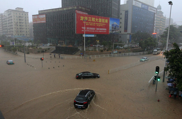 A car (bottom) drives down a flooded street amid heavy rainfall in Shenzhen, Guangdong province May 11, 2014. The worst rainstorm since 2008 hit Shenzhen on Sunday, where the authorities issued a red alert for the heavy downpour, state television reported. (Photo by Reuters)