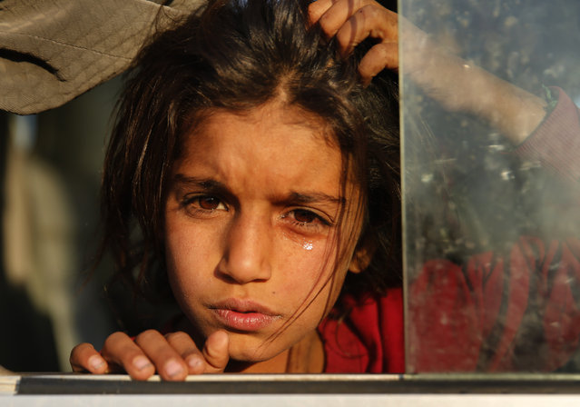 A Syrian girl who is newly displaced by the Turkish military operation in northeastern Syria, weeps as she sits in a bus upon her arrival at the Bardarash camp, north of Mosul, Iraq, Wednesday, October 16, 2019. The camp used to host Iraqis displaced from Mosul during the fight against the Islamic State group and was closed two years ago. The U.N. says more around 160,000 Syrians have been displaced since the Turkish operation started last week, most of them internally in Syria. (Photo by Hussein Malla/AP Photo)