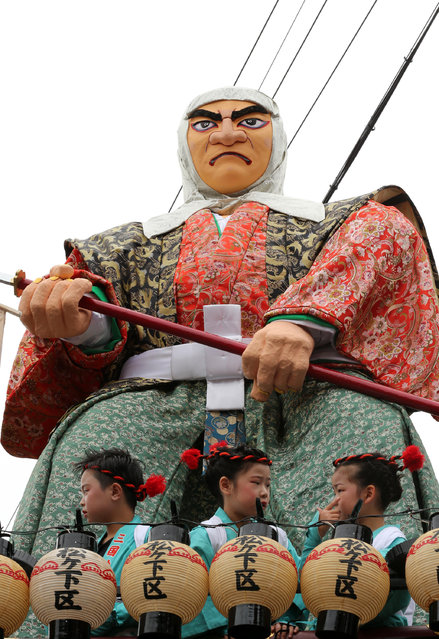 Children dressed in festival costume sit on the huge paper doll of historical Japanese figure named Hashi-Benkeii on the carts during the Mikuini annual festival on May 20, 2014 in Sakai, Japan. The annual festival takes place from May 19-21 and is attended by thousands of visitors. During the festival people dressed in traditional Japanese costumes pull carts carrying 6 meter high dolls of Japanese historical figures through the narrow streets. The origins of the festival are unclear but its history can be traced back more than 250 years. (Photo by Buddhika Weerasinghe/Getty Images)