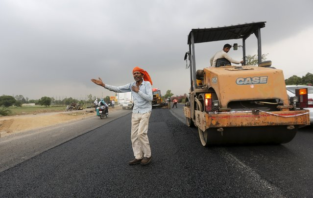 A labourer directs traffic at the construction site of the Delhi-Jaipur national highway in Manesar in the northern state of Haryana, India, July 9, 2015. (Photo by Adnan Abidi/Reuters)