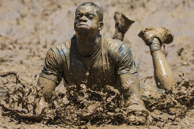 """In this Sunday, June 28, 2015 photo, Geoff Green, of Columbus, Ohio, braces himself during the """"Mud Mile"""" obstacle during a Tough Mudder event in Sparta, Ky. The obstacle course features a non-competitive format where teams assist each other through miles of running, jumping, climbing, and crawling on their way to the finish line, all for the sake of a fun challenge. (Photo by John Minchillo/AP Photo)"""