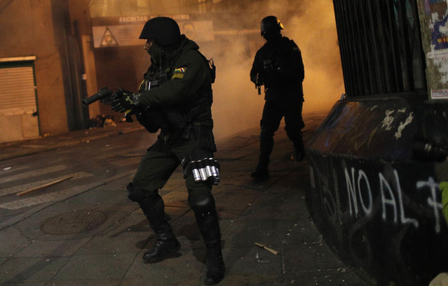 A riot police prepares to launch tear gas to disperse protesters who are against the reelection of President Evo Morales, in La Paz, Bolivia, Thursday, October 31, 2019. Violence has escalated since Morales was declared the winner of the Oct. 20 vote amid delays in the vote count. The opposition alleges the outcome was rigged to give Morales enough of a majority to avoid a runoff election; the president denies any irregularities. (Photo by Juan Karita/AP Photo)
