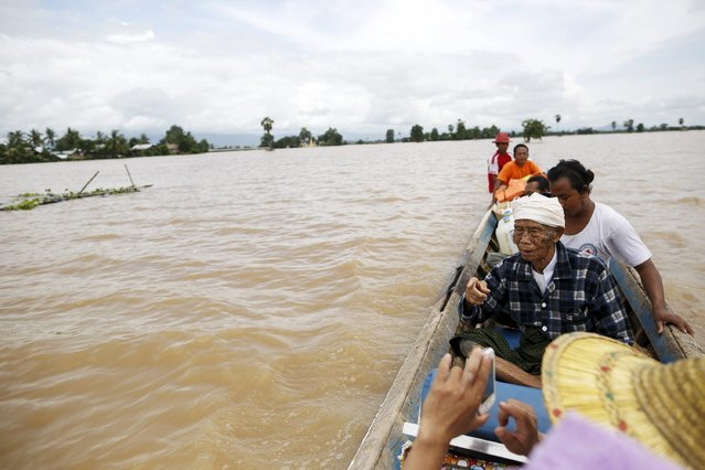 People travel on a boat over flooded rice fields in Kawlin township, Sagaing division, Myanmar, July 21, 2015. (Photo by Soe Zeya Tun/Reuters)