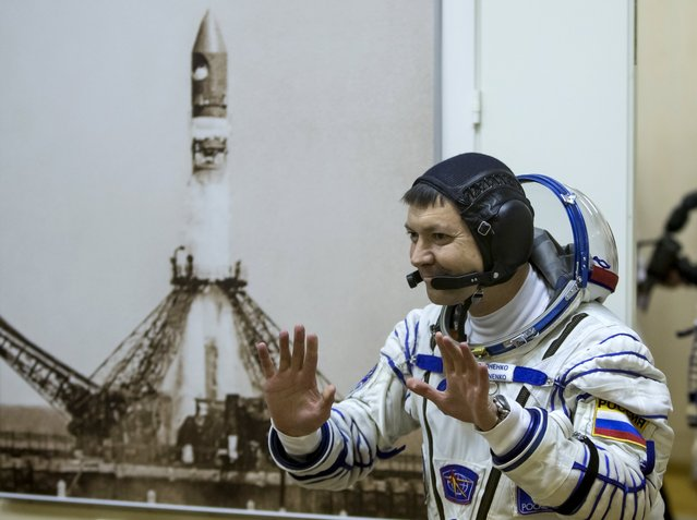 The International Space Station (ISS) crew member Oleg Kononenko of Russia waves after donning his space suit at the Baikonur cosmodrome, Kazakhstan, July 22, 2015. (Photo by Shamil Zhumatov/Reuters)