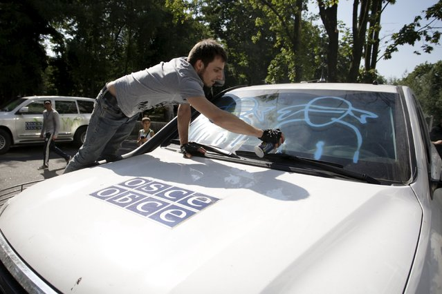 A demonstrator sprays graffiti on a truck of the Organisation for Security and Co-operation in Europe (OSCE) during a protest to demand what protesters say is true information from the OSCE about the shelling in Donetsk, Ukraine, July 23, 2015. (Photo by Alexander Ermochenko/Reuters)