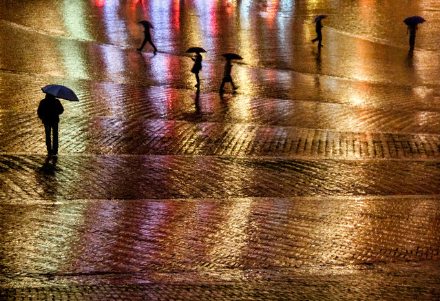 """Rainy Night in the Piazza del Campo"". It was a long day of travel and I arrived in Siena tired, hungry and a bit lonely after a few weeks of traveling alone. The rain was steady and did little to help my mood. Still, I wandered the streets until I found myself at the edge of the Piazza del Campo and was immediately drawn to the neon glow cast by the cafes along its periphery, reflecting off the wet bricks and providing an amazing backdrop for the silhouettes of umbrella'd figures making their way home on this rainy night. (Photo and caption by Karen Messerman/National Geographic Photo Contest)"