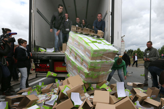 French farmers empty a truck in front of Lactalis' factory, in Laval, western France, in order to stop importation of foreign meat and milk products in France, Monday, July 27, 2015. (Photo by David Vincent/AP Photo)