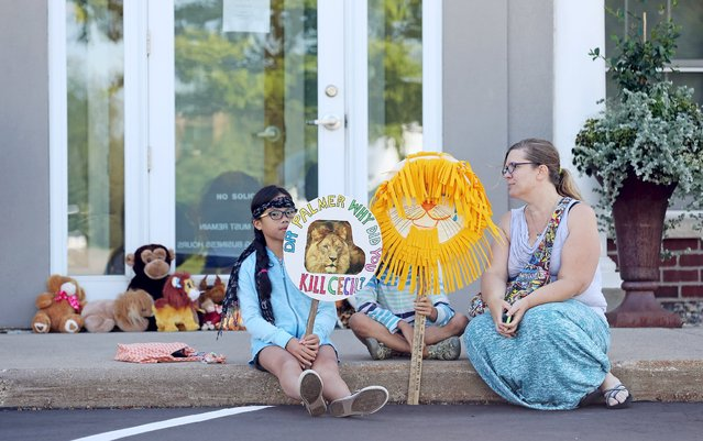 Hayley Hoppe (R) sits with her daughters Piper, 10, (L) and Paisley, 8, (C), in front of the doorway of River Bluff Dental clinic in protest against the killing of a famous lion in Zimbabwe, in Bloomington, Minnesota July 29, 2015. (Photo by Eric Miller/Reuters)