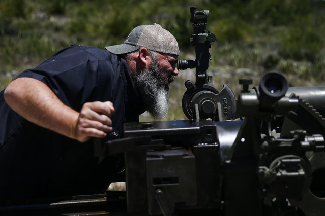 In this May 24, 2017, photo, DriveTanks.com owner Todd DeGidio aims a 105mm Howitzer WWII Artillery Piece before guests fire it at a hillside during their Allies and Axis all-day experience at Ox Ranch in Uvalde, Texas. (Photo by Michael Ciaglo/Houston Chronicle via AP Photo)
