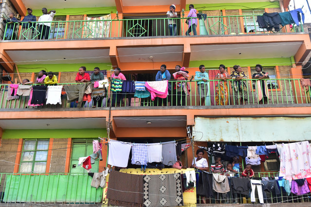 Curious onlookers stand on balconies next to the scene of a collapsed six-storey building in Nairobi, as search and rescue continue, on December 6, 2019. (Photo by Simon Maina/AFP Photo)