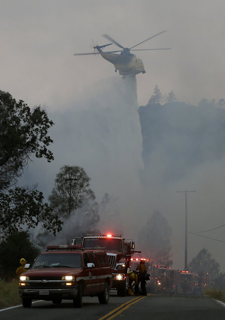 A helicopter drops water over fires along Morgan Valley Road near Lower Lake, Calif., Friday, July 31, 2015. (Photo by Jeff Chiu/AP Photo)