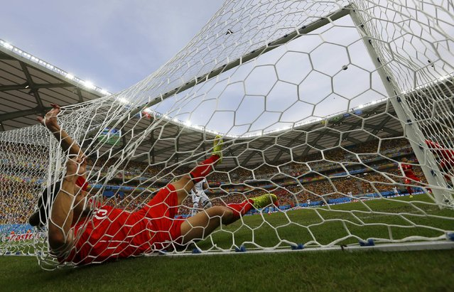 Switzerland's Ricardo Rodriguez falls into the goal net after making a save during their 2014 World Cup Group E soccer match against Honduras at the Amazonia arena in Manaus June 25, 2014. (Photo by Michael Dalder/Reuters)