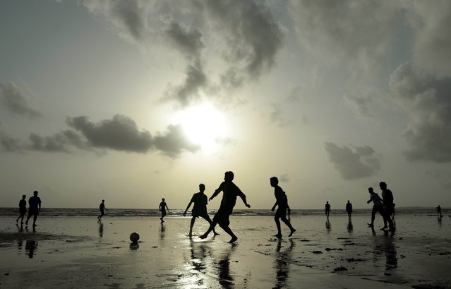 Indian youths play football at Juhu beach in Mumbai on June 24, 2014. (Photo by Punit Paranjpe/AFP Photo)