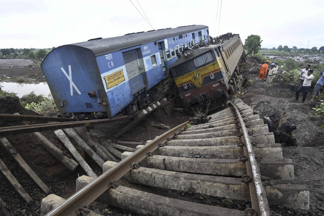 People gather at the scene where two trains derailed near the town of Harda in Madhya Pradesh state, India, Wednesday, August 5, 2015. (Photo by AP Photo)