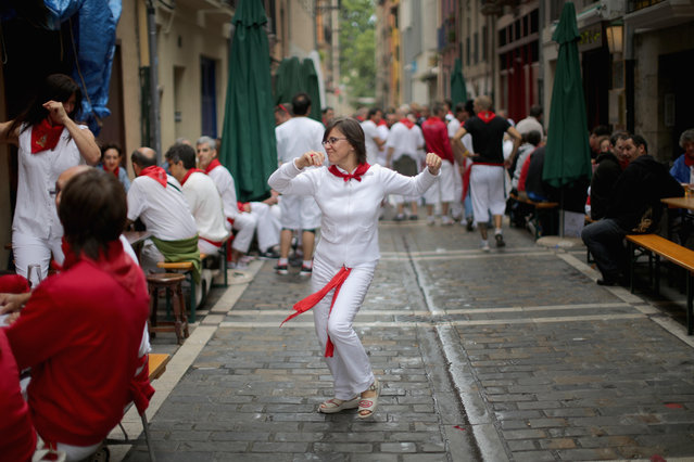 """Locals dance in the street during the second day of the San Fermin Running Of The Bulls festival, on July 7, 2014 in Pamplona, Spain. The annual Fiesta de San Fermin, made famous by the 1926 novel of US writer Ernest Hemmingway """"The Sun Also Rises"""", involves the running of the bulls through the historic heart of Pamplona. (Photo by Christopher Furlong/Getty Images)"""