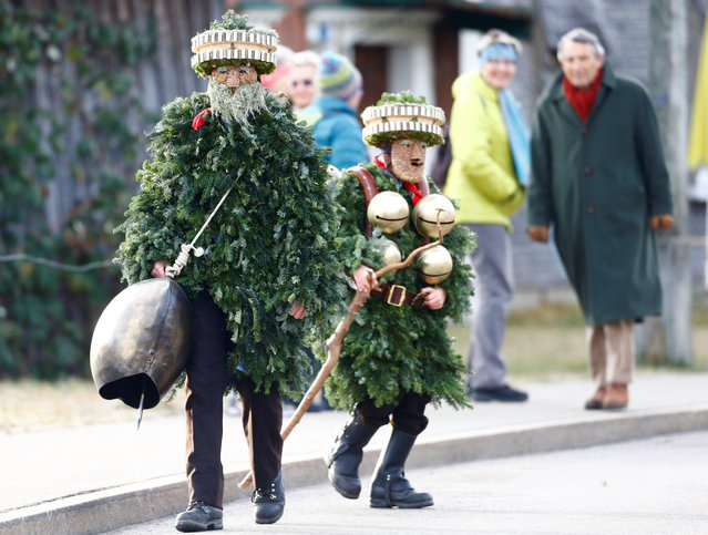 """Men dressed as """"Chlaeuse"""", figures that scare away evil spirits, carry round bells and cowbells during the traditional """"Sylvesterchlausen"""" in near the northeastern village of Urnaesch, Switzerland on January 13, 2020. (Photo by Arnd Wiegmann/Reuters)"""