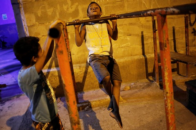A boy does pull-ups from a metal bar outside the Luta pela Paz (Fight for Peace) boxing school, in the Mare favela of Rio de Janeiro. (Photo by Nacho Doce/Reuters)