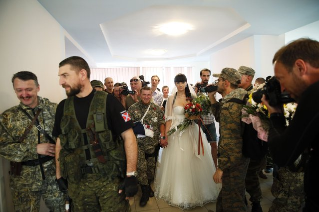 "Pro-Russian separatist Arsene Pavlov, call sign ""Motorola"", and his bride Elena walk surrounded by fellow separatists during a marriage ceremony in the registry office of the city of Donetsk July 11, 2014. (Photo by Maxim Zmeyev/Reuters)"