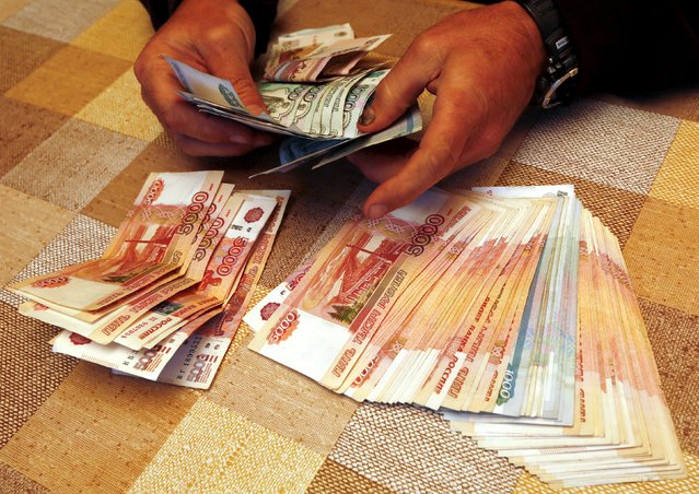 A local businessman, the owner of a tourist camp, counts Russian roubles earned during the weekend at a tourist base outside the Siberian city of Krasnoyarsk, Russia, August 9, 2015. Russia's largest gas producer Gazprom beat expectations with a 71 percent jump in first-quarter net profit after weakness in the rouble more than compensated for a drop in sales volumes to Europe. (Photo by Ilya Naymushin/Reuters)
