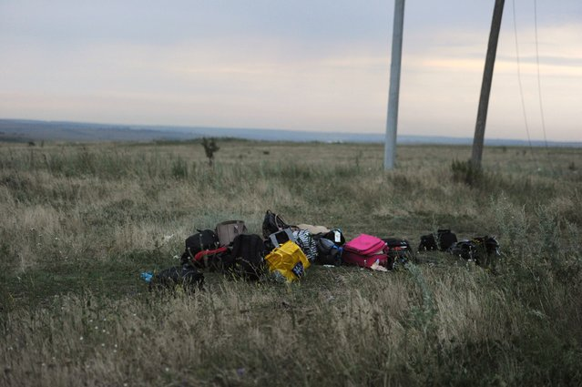 Luggages are pictured on July 17, 2014 on the site of the crash of the malaysian airliner carrying 295 people from Amsterdam to Kuala Lumpur, near the town of Shaktarsk, in rebel-held east Ukraine. Pro-Russian rebels fighting central Kiev authorities claimed on Thursday that the Malaysian airline that crashed in Ukraine had been shot down by a Ukrainian jet. (Photo by Dominique Faget/AFP Photo)