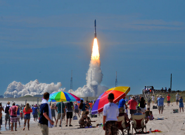 Hundreds of people pack the Canaveral national seashore's Playalinda Beach as a United Launch Alliance Atlas V rocket, carrying a U.S. Navy communications satellite, lifts off from Complex 41 at the Cape Canaveral Air Force Station, Friday, June 24, 2016, in Cape Canaveral, Fla. The satellite is designed to significantly improve ground communications for U.S. forces on the move. (Photo by Craig Rubadoux/Florida Today via AP Photo)