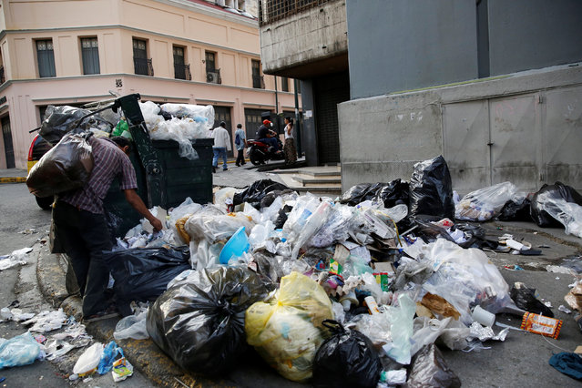 A man searches garbage in Caracas, Venezuela, June 23, 2016. (Photo by Mariana Bazo/Reuters)