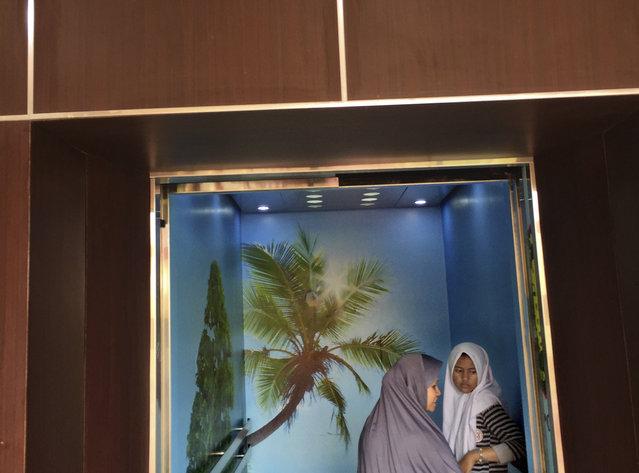 In this Friday, March 3, 2017 photo, Muslim women stand inside an elevator decorated with tree wallpapers at a hospital in Jakarta, Indonesia. (Photo by Dita Alangkara/AP Photo)