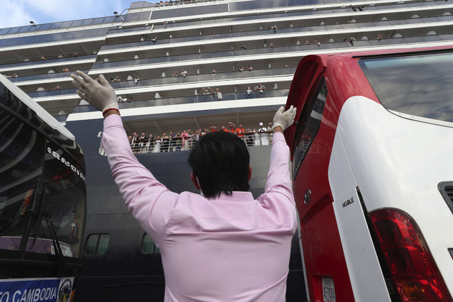 A man waves to passengers of the MS Westerdam, owned by Holland America Line, docked at the port of Sihanoukville, Cambodia, Friday, February 14, 2020. Hundreds of cruise ship passengers long stranded at sea by virus fears cheered as they finally disembarked Friday and were welcomed to Cambodia. (Photo by Heng Sinith/AP Photo)