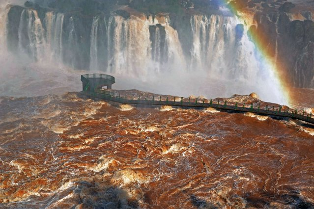 View of a damaged bridge at the Iguacu Falls on June 12, 2014, in Foz do Iguacu, Brazil, following the overflowing of the Parana river. In neighbouring Paraguay flooding has forced the evacuation of about 150,000 people in Paraguay's capital city Asuncion, authorities said. (Photo by Norberto Duarte/AFP Photo)