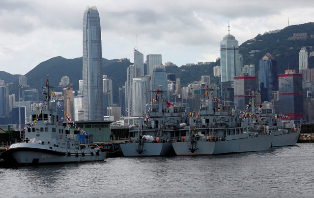 People's Liberation Army military vessels station at a naval base, with the financial Central district seen at background, during an open day celebrating the 19th anniversary of Hong Kong's handover to Chinese sovereignty from British rule, in Hong Kong July 1, 2016. (Photo by Bobby Yip/Reuters)