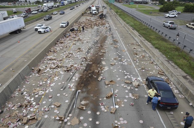 This Wednesday, August 9, 2017, photo provided by the Arkansas Department of Transportation shows Arkansas highway Interstate 30, a cross-country route that was shut down in both directions for a time Wednesday, after an 18-wheeler was sliced open during an crash and spilled frozen pizzas across the road south of Little Rock, Ark. The interstate, was closed for several hours while crews cleaned up the mess. (Photo by Rusty Hubbard/Arkansas Department of Transportation via AP Photo)