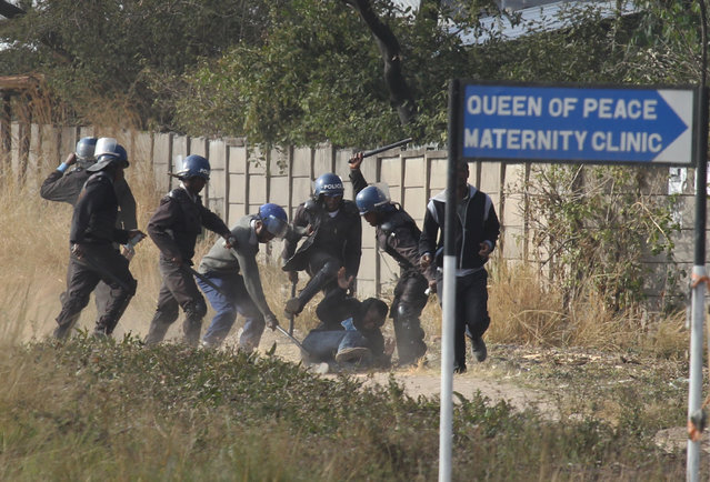 Armed Zimbabwean police surround a rioter in Harare, Monday, July, 4, 2016. (Photo by Tsvangirayi Mukwazhi/AP Photo)