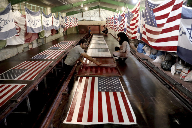In this Saturday, February 8, 2020 photo, workers print U.S. flags using a silkscreen, at the Diba Parcham Khomein factory in Heshmatieh village, a suburb of Khomein city, in central Iran. Workers at a small Iranian factory diligently add all 50 stars and 13 bars to American flags while carefully imprinting the Star of David on those of Israel. That's even as all their work is destined to go up in smoke. This factory serves as a major producer for the American and Israeli flags constantly burned at demonstrations in the Islamic Republic. (Photo by Ebrahim Noroozi/AP Photo)