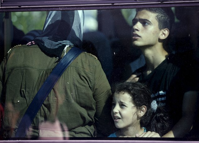 """A Syrian refugee girl looks out from a bus window following her arrival onboard """"Eleftherios Venizelos"""" passenger ship at the port of Piraeus near Athens, Greece, August 20, 2015. (Photo by Stoyan Nenov/Reuters)"""