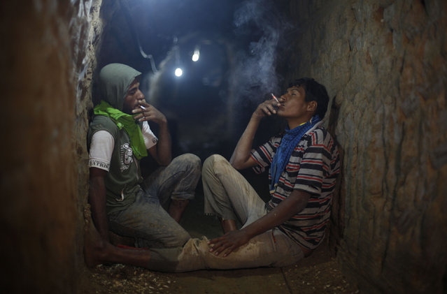 Palestinian tunnel workers smoke cigarettes as they rest inside a smuggling tunnel flooded by Egyptian security forces, beneath the Gaza-Egypt border in the southern Gaza Strip September 10, 2013. (Photo by Ibraheem Abu Mustafa/Reuters)