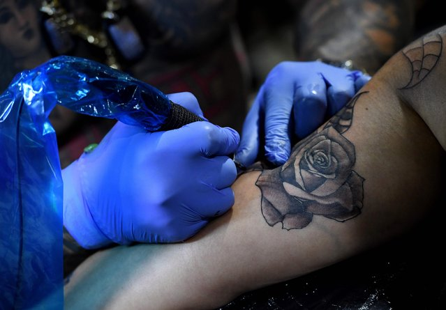 Tattoo artist Blaise Moreno from King Blaise Studio, works on a tattoo for Veronica Angel at the LA Tattoo Convention in Long Beach, California, on August 19, 2017. (Photo by Mark Ralston/AFP Photo)