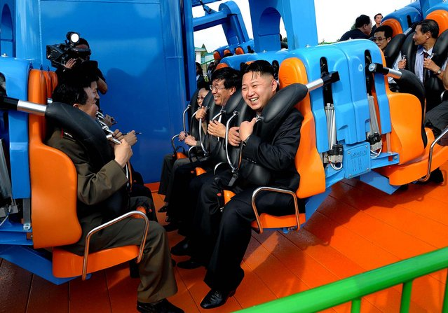 In this undated photo released by the Korean Central News Agency, North Korean leader Kim Jong Un, center, reacts on a ride as he attends the completion ceremony of the Rungna People's Pleasure Ground in Pyongyang on July 26, 2012. (Photo by Korean Central News Agency via Korea News Service)