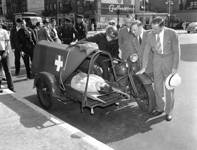 Developed for the British American Ambulance Corps, this new motorcycle ambulance is capable of speeding wounded soldiers 90 miles an hour from the front lines to field hospitals. Its springs are synchronized with the patient?s heartbeat to avoid increasing fever when traveling over various Terrain. Viewing it in New York  August 27, 1941, are left to right: constable Herbert Scott of England, driver; William E. Detlor, whose firm developed the vehicle; M. W. Stand, inspector-general of Civilian Defense, and Maj. Edward Riekert, also. (Photo by AP Photo)
