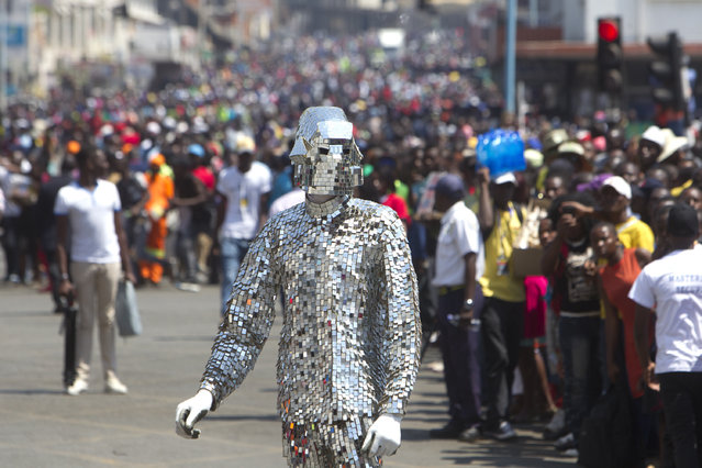 In this picture taken Saturday, September 9, 2017, a Zimbabwean street performer wears a suit made from glass on the streets of Harare during the International Carnival in the capital. (Photo by Tsvangirayi Mukwazhi/AP Photo)